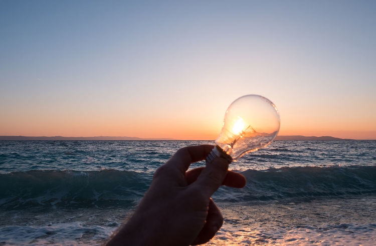 Beach sunset and man holding light bulb against sun concept Beauty In Nature Bulb Close-up Concept Electricity  Energy Environment Holding Horizon Over Water Human Hand Idea Inovation Light Man Nature One Person Outdoors People Power Sea Shape Sky Sunlight Sunset Water