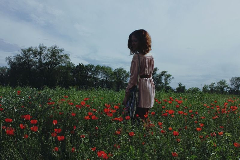 Woman Standing Amidst Poppies On Field