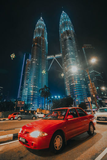Kuala Lumpur, Malaysia, May 1st, 2019 : A national car, Proton Wira in red colour in front of Malaysia's most famously known KLCC