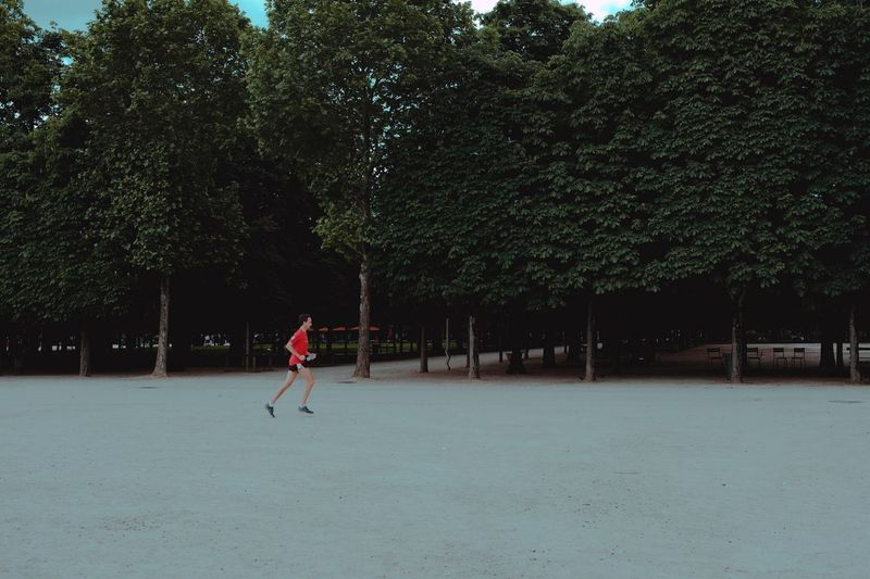 Man playing on field against trees