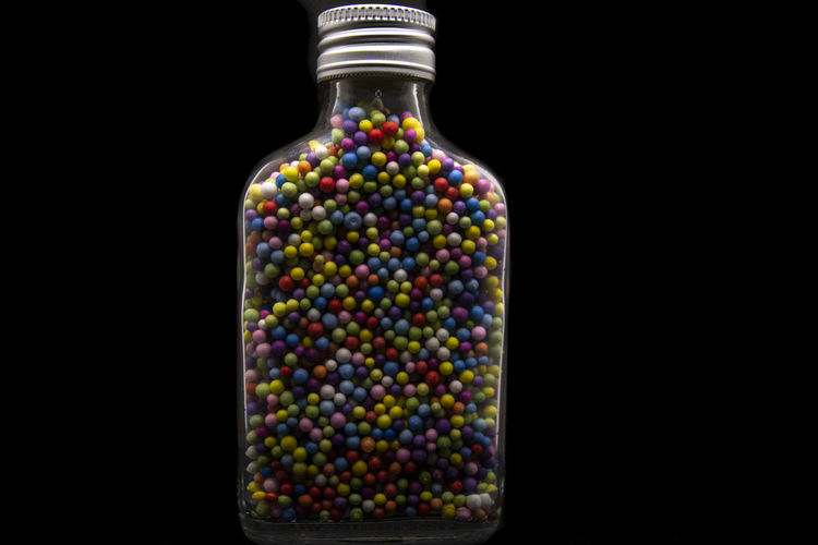 Close-up of multi colored glass bottle against black background