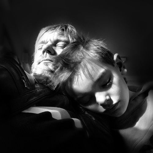 Close-Up Of Grandfather And Grandson Sleeping In Darkroom
