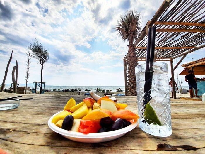 Food on table at beach against sky