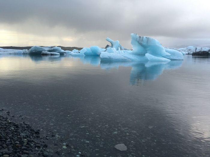 Iceberg In Sea Against Cloudy Sky At Glacier Lagoon