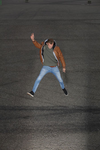 Full length of young man jumping over road