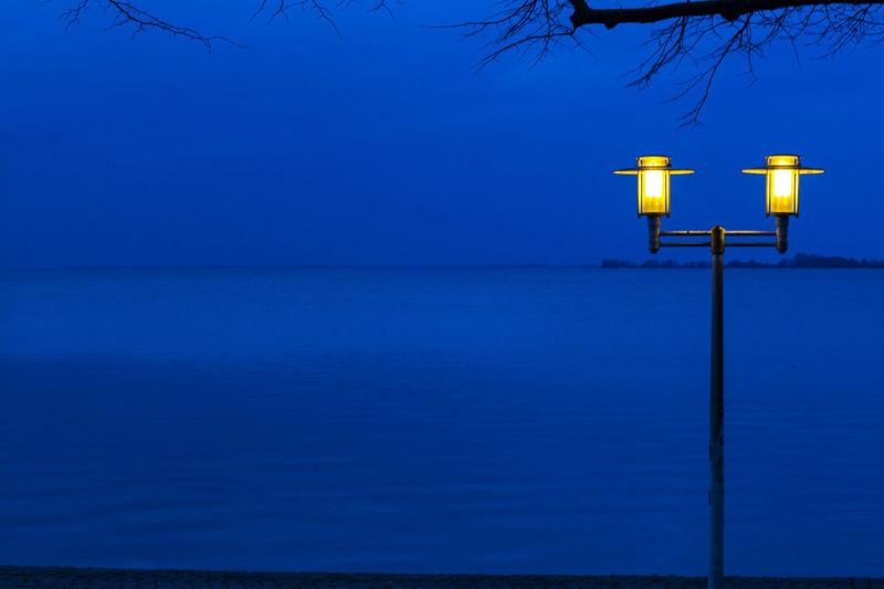 Illuminated light by sea against clear blue sky