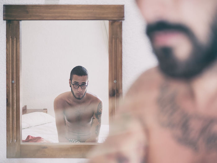 Portrait of shirtless man reflecting in mirror with friend in foreground