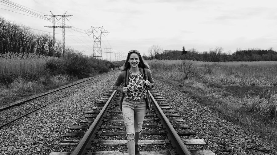 Portrait of woman on railroad track against sky