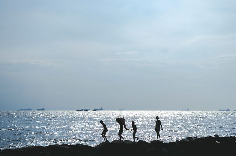 Four children walking on coastline