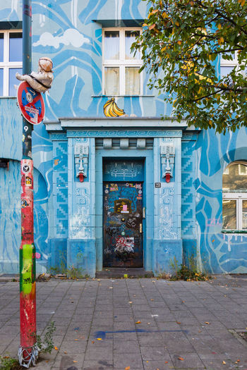 Cheeky Monkey Architecture Built Structure Building Exterior No People Day Footpath Outdoors Plant Düsseldorf Deutschland Germany Flingern Süd Graffiti Painting City Sidewalk Street Entrance Art And Craft Mural Door Nature Tree Bananas Doll