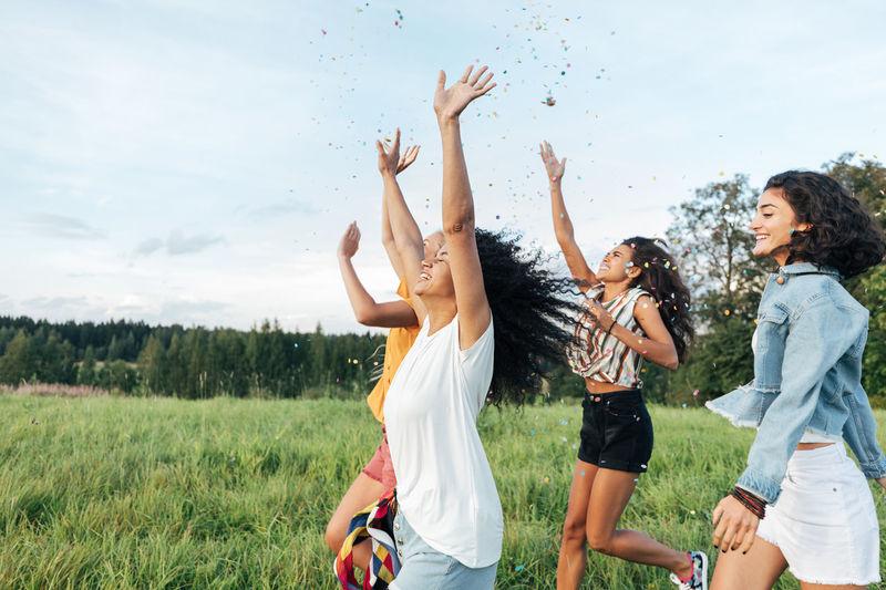 Friends enjoying on field against sky