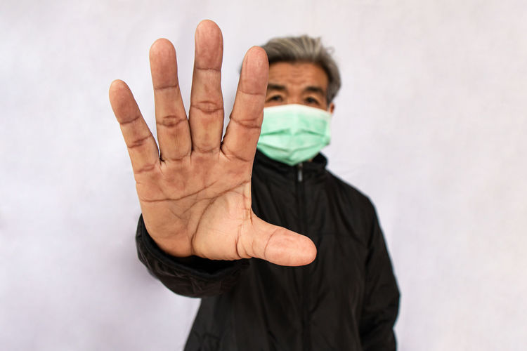 Senior woman in mask gesturing against white wall