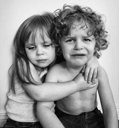 Cute girl embracing crying brother against wall at home