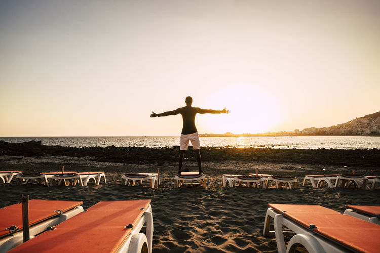 epic image for black race african man standing on a sunbed on the beach looking and enjoying the golden sunset in front of him. Canary Islands African Ethnicity Arms Outstretched Arms Raised Beautiful Model Beauty In Nature Freedom Full Length Horizon Over Water Human Arm Human Limb Leisure Activity Lifestyles Limb Nature One Person Outdoors Real People Rear View Scenics - Nature Sea Sky Standing Sunset Water
