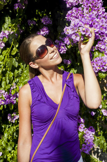 Close-up of woman by purple flowers