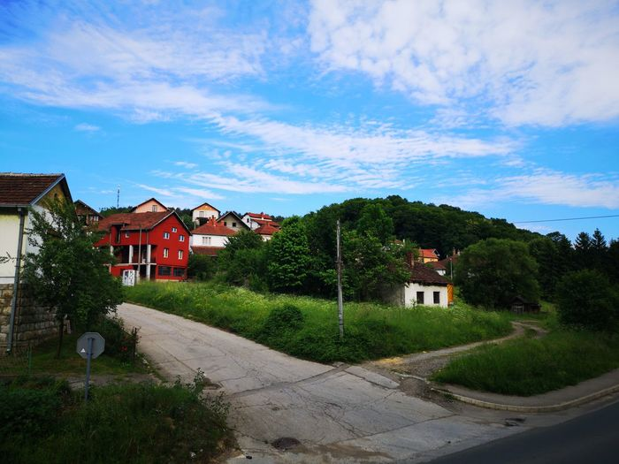 Road amidst houses and buildings against blue sky