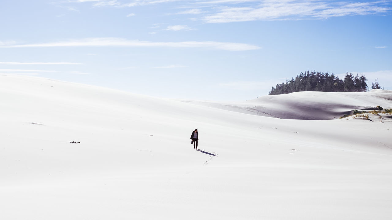Full length of woman standing on snow against sky during sunny day