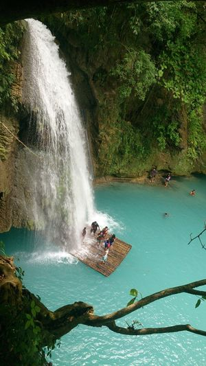 High angle view of people on wooden raft at waterfall