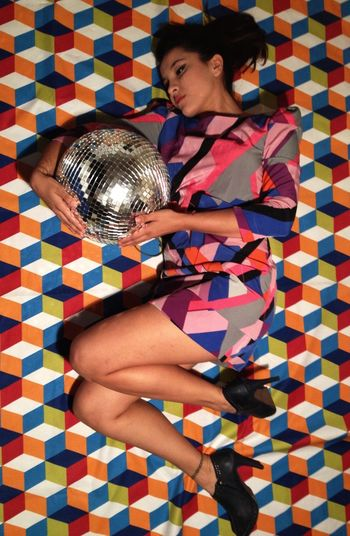 Young Woman Relaxing With Disco Ball In Bed At Home