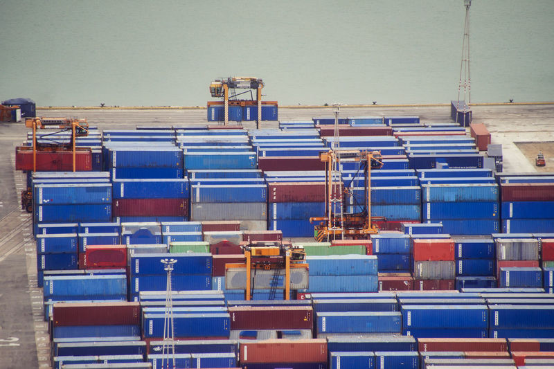 Stack of pier full of cargo container against blue sky