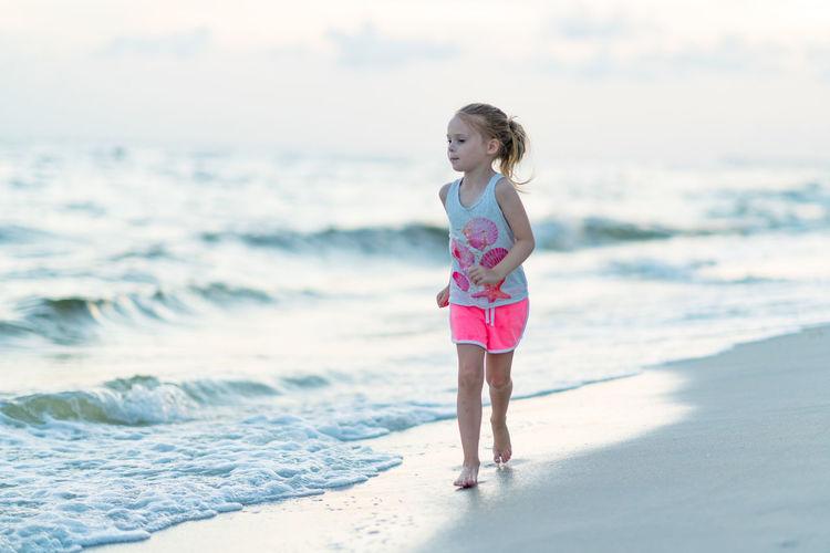 Cute girl running at seashore