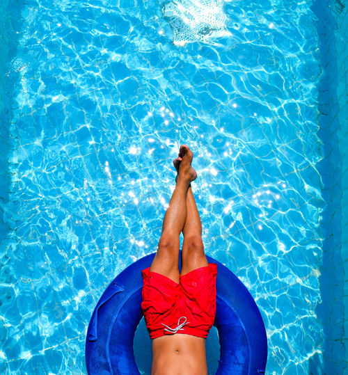 Low Section Of Man Relaxing In Inflatable Ring On Swimming Pool