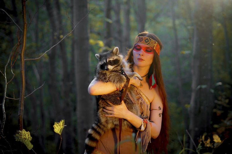 Young Woman In Traditional Clothing Carrying Raccoon In Forest