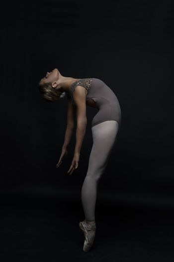 Side view of ballet dancer stretching against black background