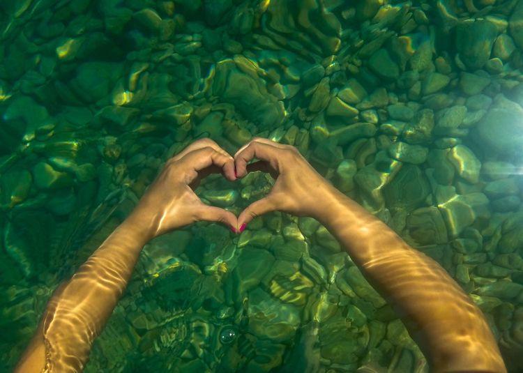 Cropped hands of woman making heart shape in sea