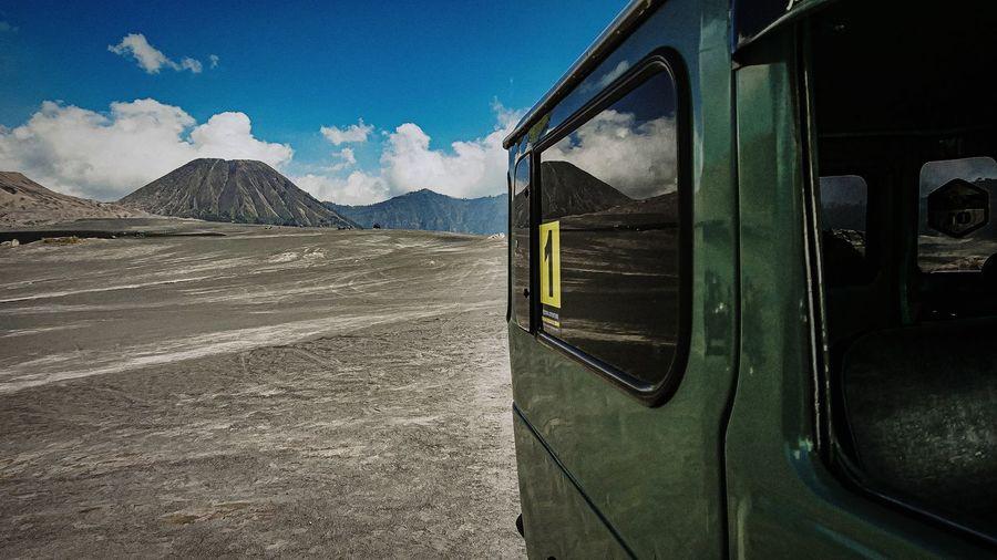 Bus on mountain against blue sky