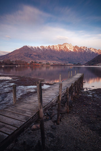 Beauty In Nature Cloud - Sky Day Idyllic Lake Mountain Mountain Range Nature No People Non-urban Scene Outdoors Pier Reflection Scenics - Nature Sky Snowcapped Mountain Tranquil Scene Tranquility Water Wood - Material Wooden Post