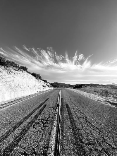 Empty road against sky during winter