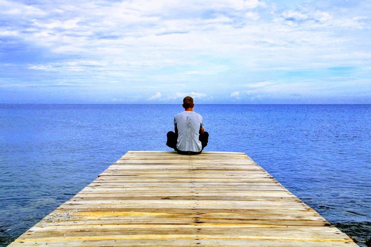 Rear view of man sitting on pier over sea against sky