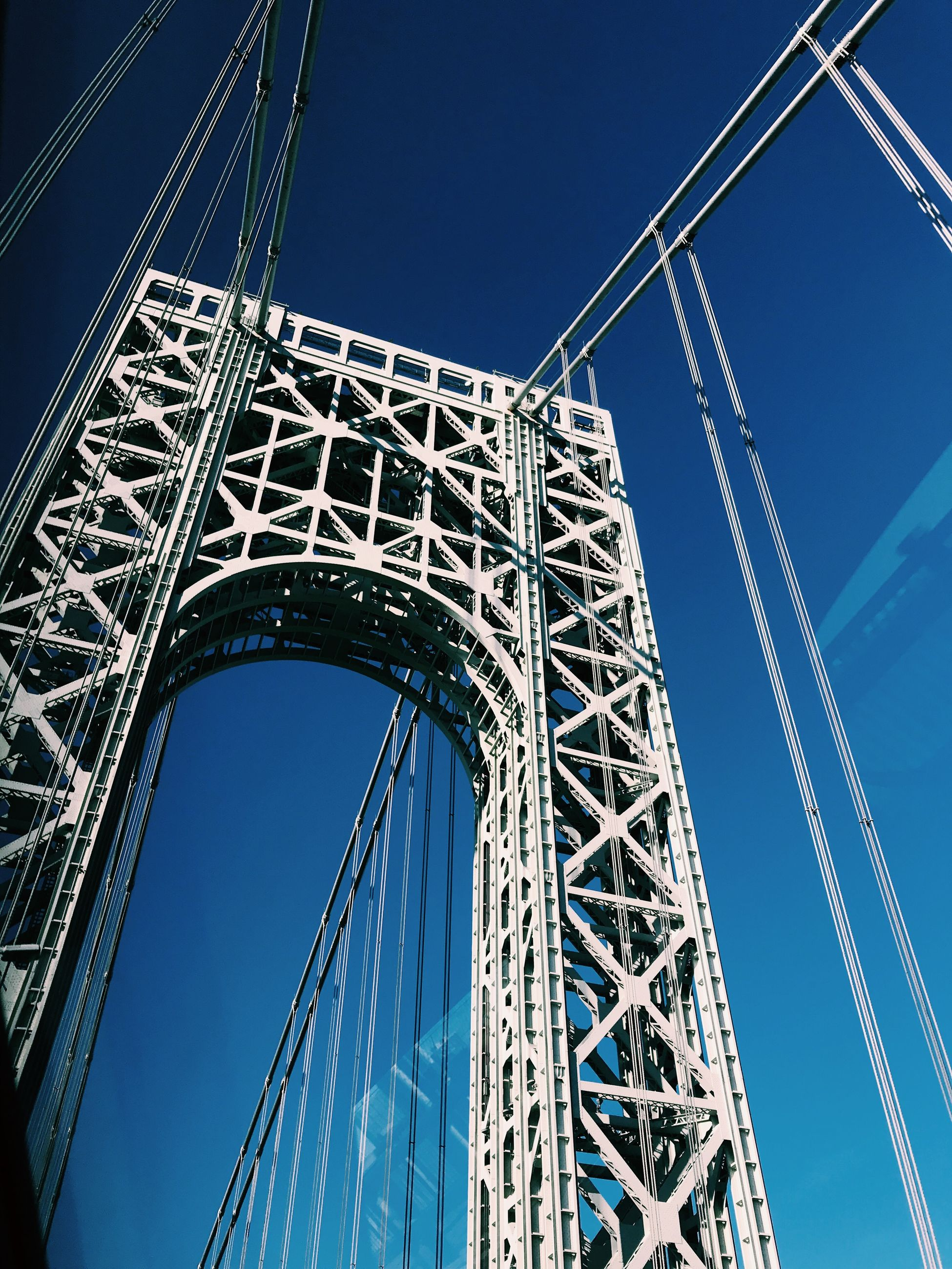 low angle view, built structure, sky, architecture, blue, metal, nature, no people, day, connection, clear sky, bridge, bridge - man made structure, outdoors, sunlight, fuel and power generation, transportation, cable, tall - high, directly below