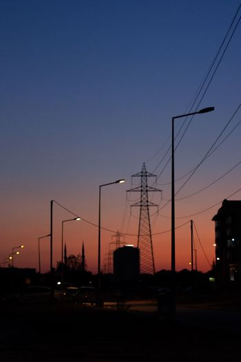 Silhouette electricity pylons against clear sky during sunset
