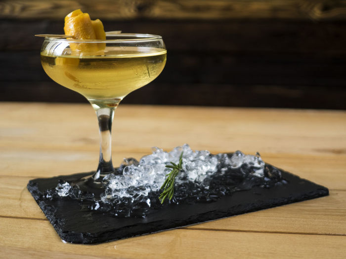 Close-up of cocktail served with ice cubes on wooden table