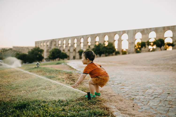 Side view of boy playing with water sprinklers