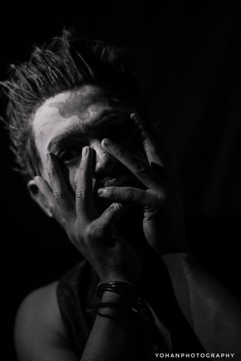 Portrait of man with hand on black background