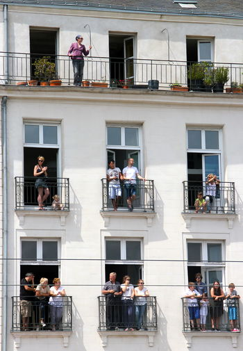 Low angle view of people standing in balcony on sunny day
