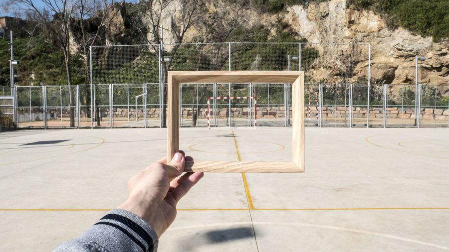 Man holding wooden frame against goal post