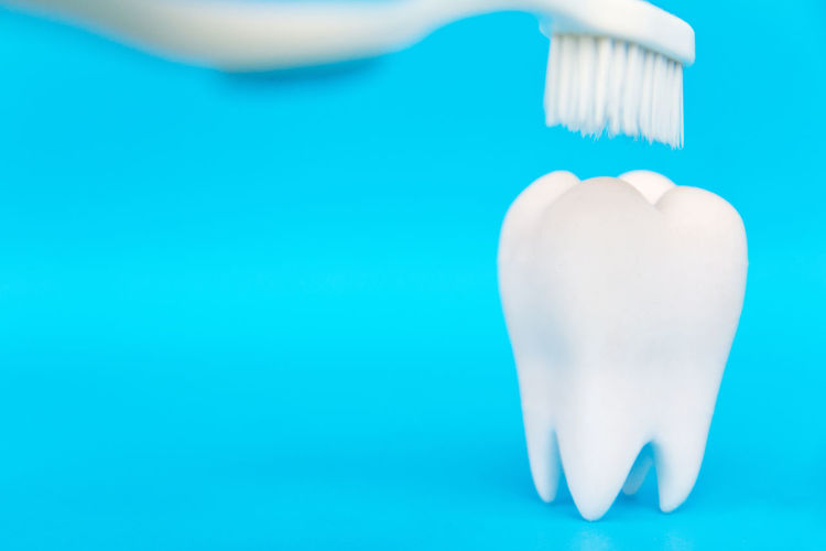 Close-up of toothbrush over dentures against blue background