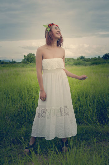 Happy young woman standing on grassy field against cloudy sky