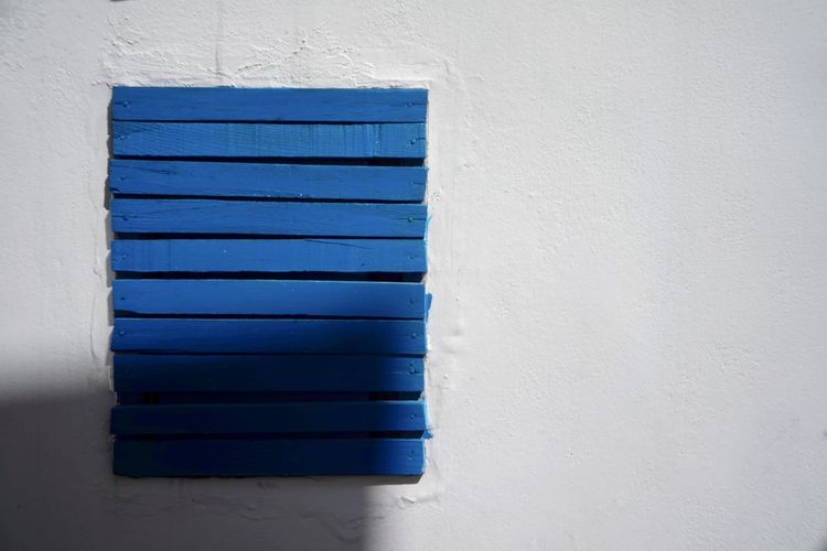 Close-up of blue window on white wall