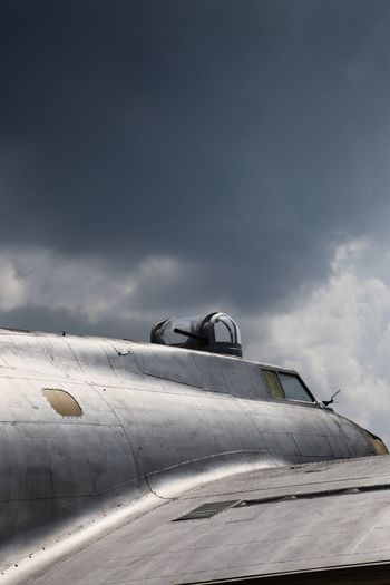 Cropped image of airplane against cloudy sky