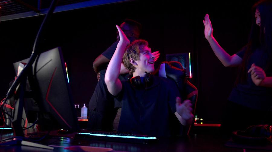 People playing video game in darkroom