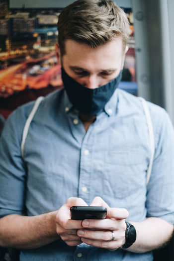 Man wearing mask using mobile phone