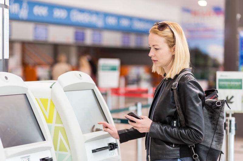 Beautiful woman using atm at airport