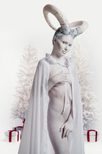Female with goat body-art isolated on white. Dedicated to Chinese Horoscope 2015 - Year of the Goat (Sheep) Aries December Goat Holiday Horns Horoscope  New Year Winter Woman Zodiac Sign Astrology Sign Beautiful Woman Body Paint Bodyart Character Christmas Decoration Christmas Tree Cloak Conceptual Female Gift Boxes Horned Naked_art Sheep Women