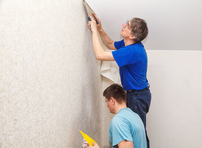 Painters putting wallpaper on wall at construction site