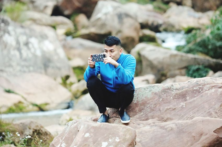Mobile Conversations Rock - Object Real People One Person Lifestyles Full Length Young Men Leisure Activity Day Young Adult Outdoors Sitting Nature Men Water Bird Lotus Position Beauty In Nature